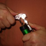 1. Place the first step of the hinged lever on the bottle lip, then raise the main body of the corkscrew.