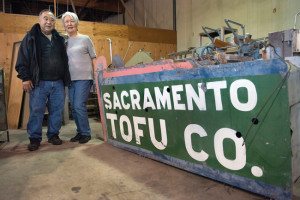 SIGN OF THE TIMES — Alvin and Dorothy Kunishi stand next to the sign which once hung over the business when it was located on 6th Street near Southside Park in the 1950s on Nov. 19, 2015, in Sacramento, Calif. The Kunishis were cleaning up the remnants of their family business, which produced fresh tofu for more than 60 years in Sacramento. photo:  Sacaramento Bee / Randy Pench The Kunishi's are cleaning up the remnants of their family business, which produced fresh tofu for more than 60 years in Sacramento.