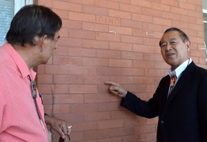 TRACING HISTORY — Ambassador Ichiro Fujisaki points to Japanese writing etched into the brick wall of a building at United Tribes Technical College, the site of a former federal government detention camp during World War II. United Tribes President David M. Gipp at left. photo by Dennis J. Neumann / United Tribes News