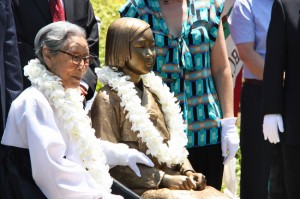 MEMORIAL UNVEILED —  Kim Bok Dong (L), 87, sits next to a bronze statue of a girl in traditional Korean clothing — a memorial for women forced into sexual slavery for the Imperial Japanese military — at Glendale Central Park near Los Angeles on July 30. Kim said she spent eight years providing sexual services to Japanese troops after she was forcibly drafted when just 14 years old.  Kyodo News photo