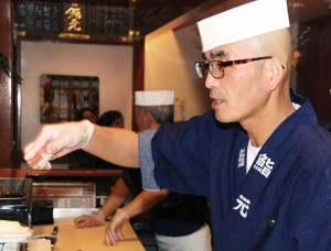 "California's Sushi chefs have their hands full with new law — An employee at popular restaurant Sushi Gen in Los Angeles, picks up sushi with gloves on Feb. 4. Under a new California law implemented Jan. 1, food employees are not allowed to contact ""ready-to-eat"" foods with their bare hands except when washing fruits and vegetables. Kyodo News photo"