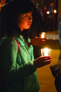 A young candle holder takes part in San Jose's Day of Remembrance Candlelight Procession through San Jose's Japantown. photo by Andy Frazer