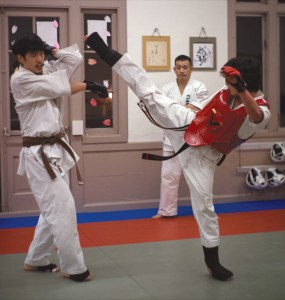 PUNCH, KICK, HANDSHAKE, BOW, REPEAT — Naohiro Tomiyama (above right) at his karate dojo.  photo by Daisuke Tagawa