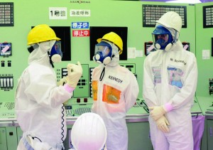 U.S. envoy Kennedy visits DAIICHI — U.S. Ambassador to Japan Caroline Kennedy (C) and her son Jack Schlossberg (R) wearing protective suits and masks are briefed during their visit to the central control room for the Nos. 1 and 2 reactors at Tokyo Electric Power Co.'s Fukushima Daiichi nuclear plant in the town of Okuma, Fukushima Prefecture, on May 14. The plant was devastated by the March 2011 earthquake and tsunami. pool photo by Sankei Shimbun/Kyodo News