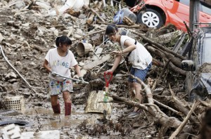 AFTERMATH OF MUDSLIDES IN HIROSHIMA— Rio Kanzaki (R), 16, and her sister Ruka, 14, remove mud from their heavily damaged house in the city of Hiroshima on Aug. 24, after the area was hit by massive mudslides following torrential rain on Aug. 20.  Kyodo News photo