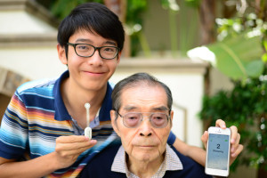 TEEN HELPS ALZHEIMER'S PATIENTS — High school student Kenneth Shinozuka (left) created a sensor to help keep track of his grandfather, Deming Feng, who suffers from Alzheimer's disease, and has a tendency to wander. The sensor transmits a signal to the caregiver's smartphone. photo by James Xue
