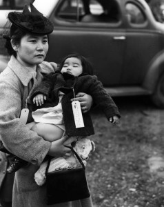ICONIC PHOTO — Fumiko Nishinaka Hayashida holds her 13-month-old daughter Natalie as she waits with other Japanese American residents of Bainbridge Island at the Eagledale Ferry Landing to be taken off Bainbridge and sent to a concentration camp in March 1942.  photo courtesy of Museum of History and Industry-Seattle Post Intelligencer Collection