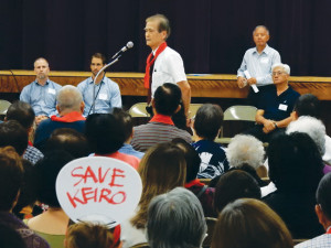 KEIRO CONTROVERSY — Dr. Kenji Irie (at microphone) speaks against the sale of Keiro facilities at an Oct. 15 community meeting. Those listening in the back row were (L to R): Ryan Case of Aspen Skilled Healthcare, Tyler Verdieck of Pacifica Companies, Shawn Miyake, president & CEO of Keiro Senior HealthCare, and Keiro board Chair Gary Kawaguchi. Cultural News photo