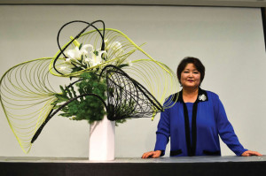 FLORAL ART — Sogetsu School of Ikebana instructor Kika Shibata poses with the arrangement she demonstrated at the Floral Artistry ikebana show. photo by Heather Ito/ Nichi Bei Weekly