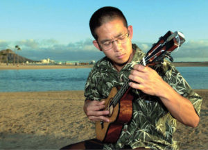 MEMORIAL SONG — Jake Shimabukuro strums a ukulele on the island of Oahu in Hawai'i in 2001, when he wrote a song titled ''Ehime Maru,'' dedicated to the victims of the sinking of the Japanese training ship Ehime Maru near Hawai'i. Shimabukuro said he wanted to do something to help relatives of the nine people presumed dead. Kyodo News photo